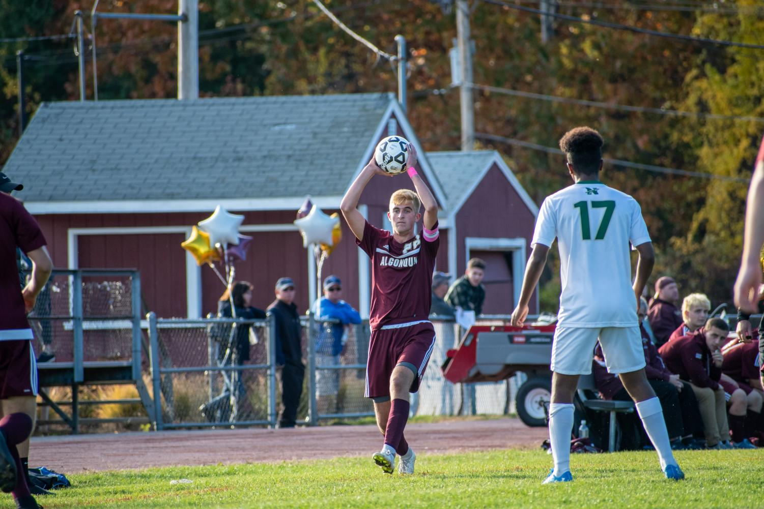 Junior captain Nick Alcock throws the ball in play against Nashoba on Oct. 26.  In addition to being a captain, Alcock has the opportunity to participate in leadership workshops held by the Athletic Council and outside workshops from the MIAA as a student ambassador.
