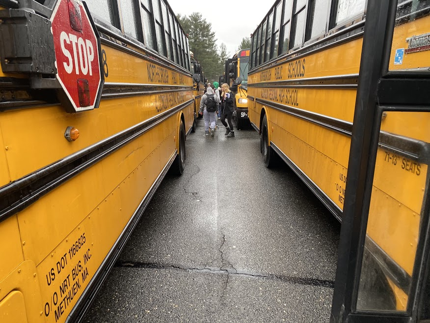 Students walk between the busses after school on a rainy December afternoon.