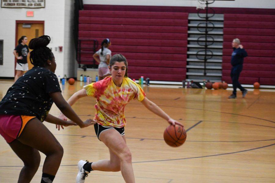 Senior Patricia Biamou guards junior Jenny Lambert at basketball tryouts.