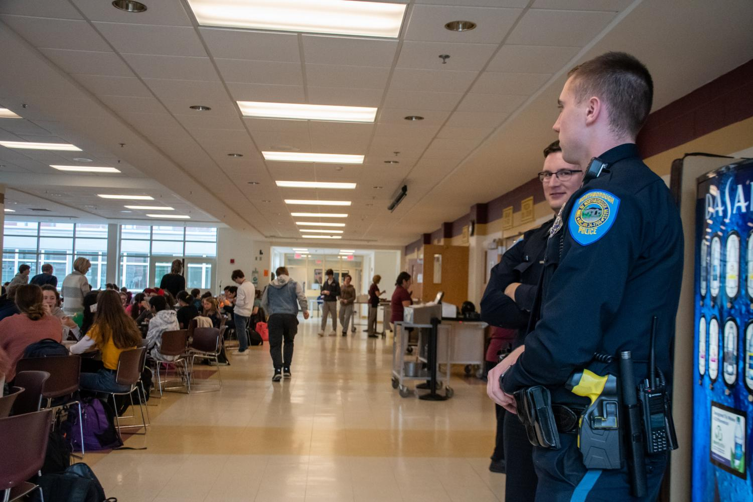 Police officers stand in the cafeteria on Dec. 10. There was an increased police presence at school after threatening statements were found written on bathroom walls.
