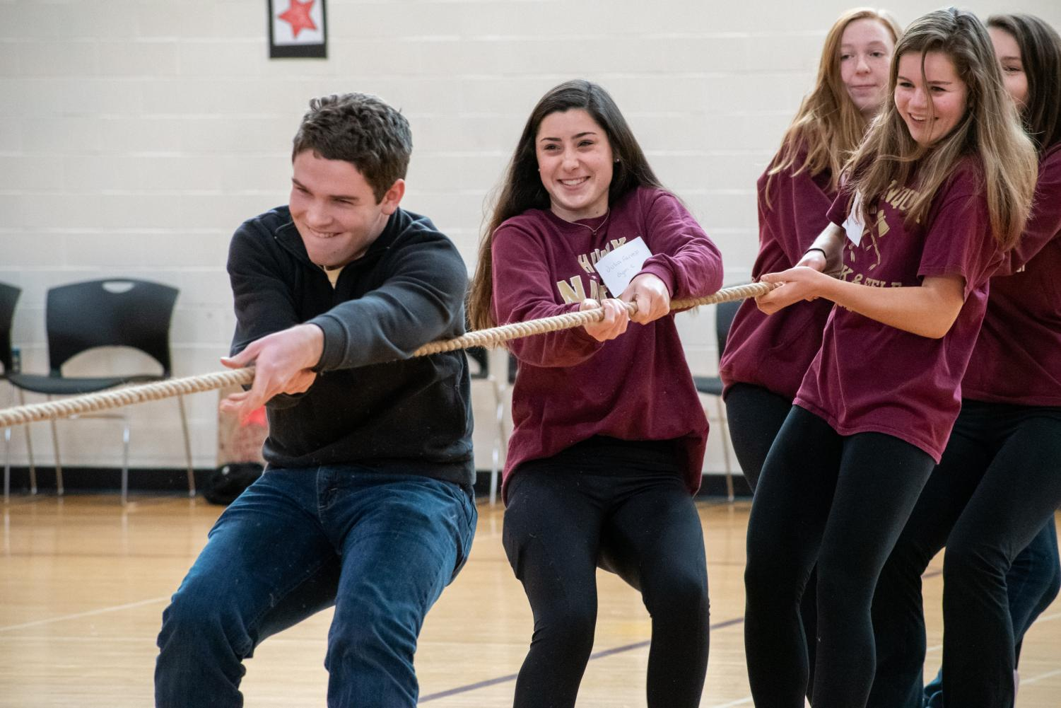 [From front to back] senior Paul Probst and juniors Julia Farrell, Maeve Grandpre and Lucy McGlynn participate in a game of tug of war as a part of Day for Change. This year, more large group activities were added in order to create a more lasting impact on freshmen.