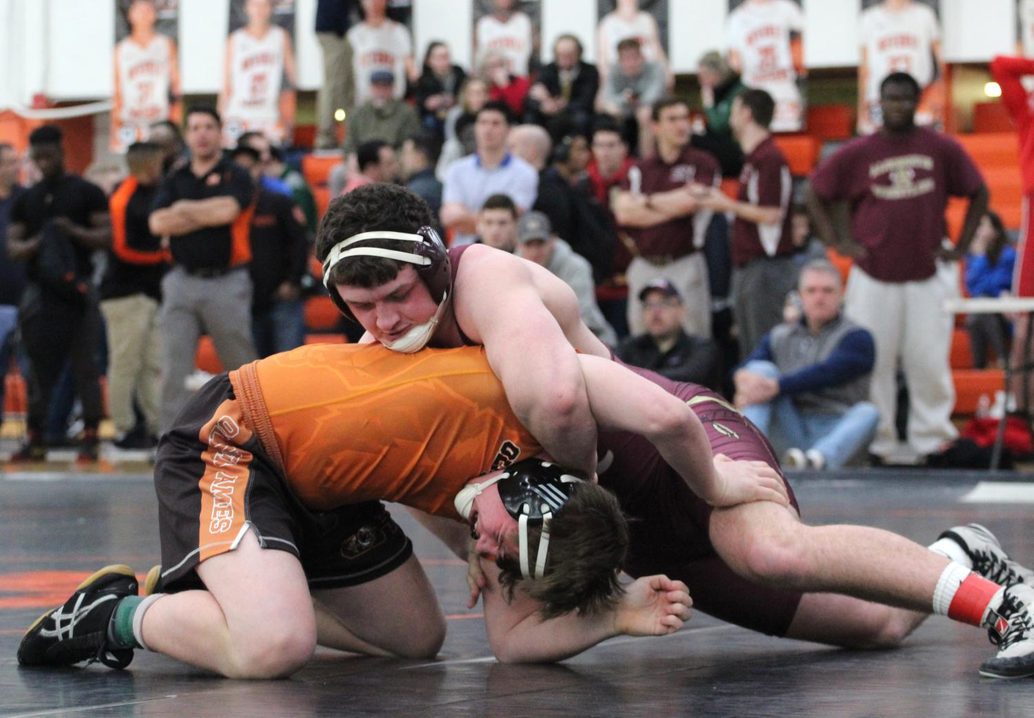 Alumnus Shea Garand pins down an opponent in the 2019 winter season.