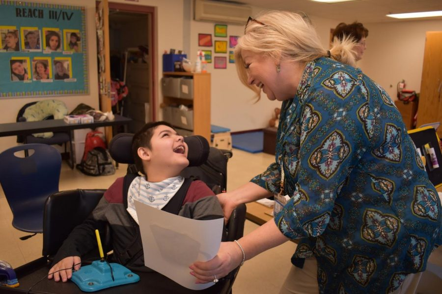 Collaborative student Nate laughs with one of his teachers, Yvonne Belcher.