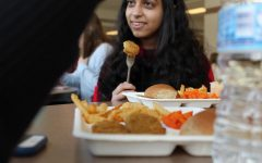 After receiving her lunch on one of the cafeteria's new paper trays, junior Sarah Saeed enjoys her chicken nuggets.