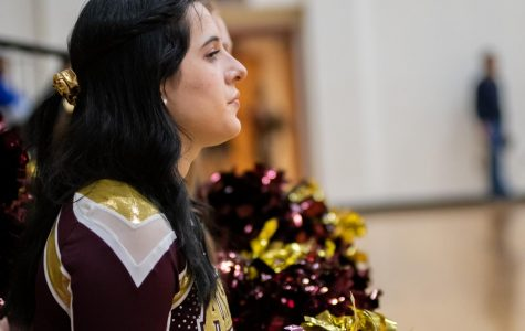 At the beginning of the boys' basketball game on Jan. 31, senior Meredith Lapidas looks out with the rest of the cheerleaders.