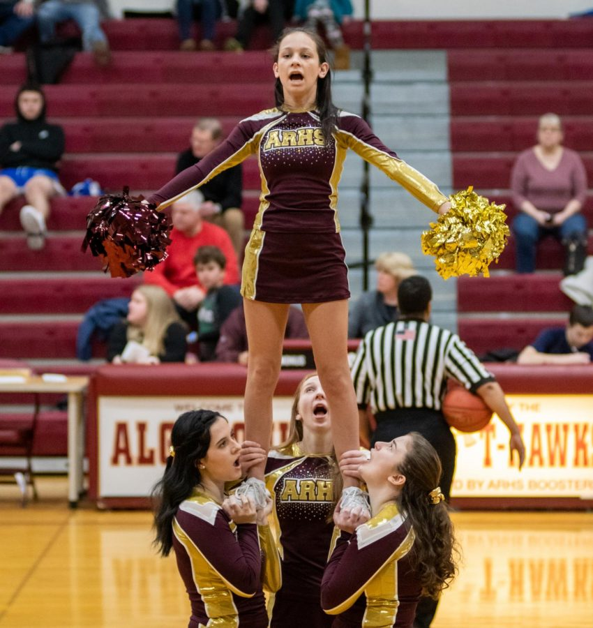 At the top of the pyramid, sophomore Isabella Gentile hypes up the crowd.