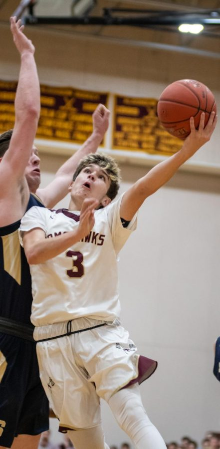 After driving to the basketball, junior Patrick Freeman attempts to lift the ball around a Shrewsbury defender. Freeman finished with 8 points.