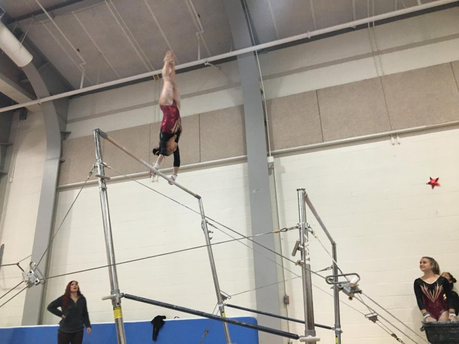Senior Sequoia Truong casts to handstand before completing her bar routine.
