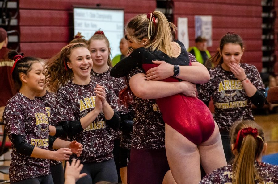 After scoring a team high 9.625 on the vault to help clinch the teams second place spot, sophomore Lizzy Debroczy celebrates with her teammates.