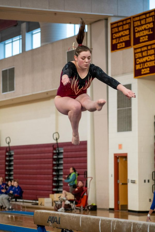 After leaping into the air from the beam, senior Sarah Middleton prepares to land back on the beam.