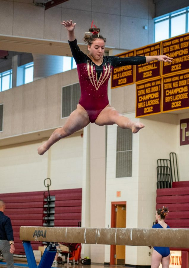 As she reaches the top of her jump, sophomore Mia Gorman focuses to land back on the beam. She finished with a score of 9.35.