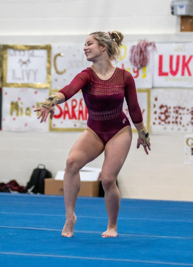 Sophomore Lizzy Debrocy performs her floor routine at a meet against