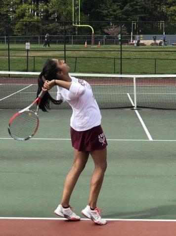 As she begins to swing overhead, senior Ruchitha Rajaghatta keeps her eye on the ball.
