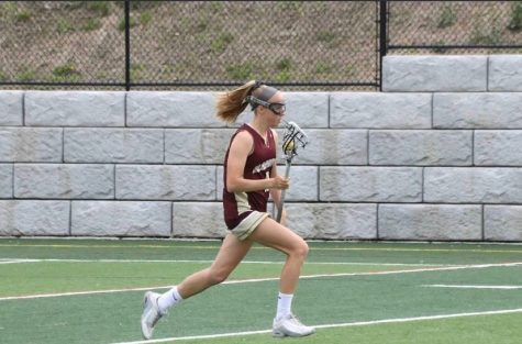 As she runs down the field, senior Olivia Chiota looks to make a move with the ball in her stick.