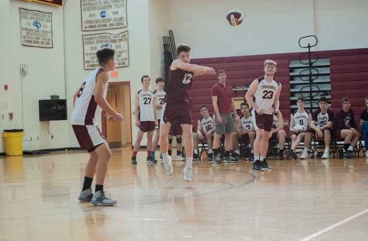 Senior Matt Keller jumps to serve the ball as his teammates watch with smiles.