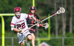 Senior Henry Alford moves toward the goal with the ball in his stick as his opponent chases after him at a home game.
