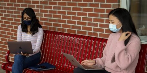 Sitting outside the rotunda, juniors Cynthia Rajeshkanna and Melissa Dai go over potential dates for tutoring.