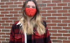Assistant A&E Editor Jessie Lambert coordinates her red mask to a red striped jacket and shoes.