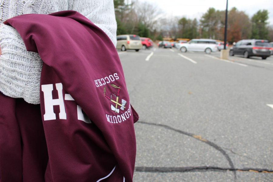 Senior Megan Harrington carries her soccer jacket displaying the tomahawk mascot, the subject of a petition calling for change written by