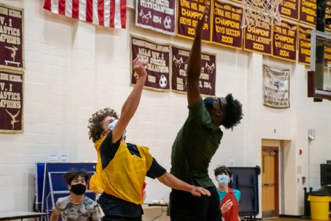 Freshmen Patrick Baimou and Brennan Rice both go up to get the ball from a rebound during the freshmen boys basketball tryouts on December 14.