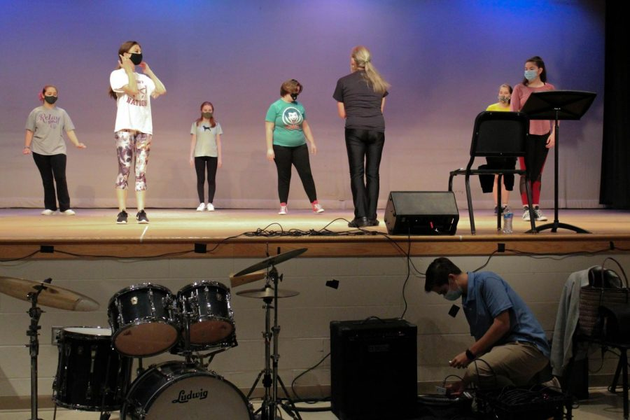 During a dance rehearsal, students work to learn the choreography while sophomore Ben Schanzer works with the tech crew to get the auditorium ready for the filming of the musical.