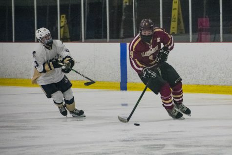 Senior captain Jack Shemligian forwards the puck toward Shrewsbury's goal in an attempt to score while an opposing defender tries to steal the puck during the January 16 game.