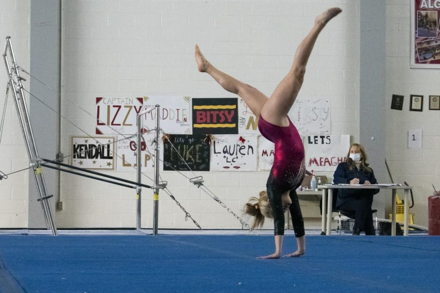 A gymnast performs a handstand during their floor routine at a meet against Westborough on Saturday, January 23.
