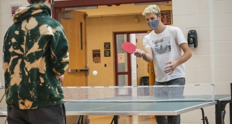 Senior Jacob Carulli plays ping pong during physical education teacher Andrew Kinney