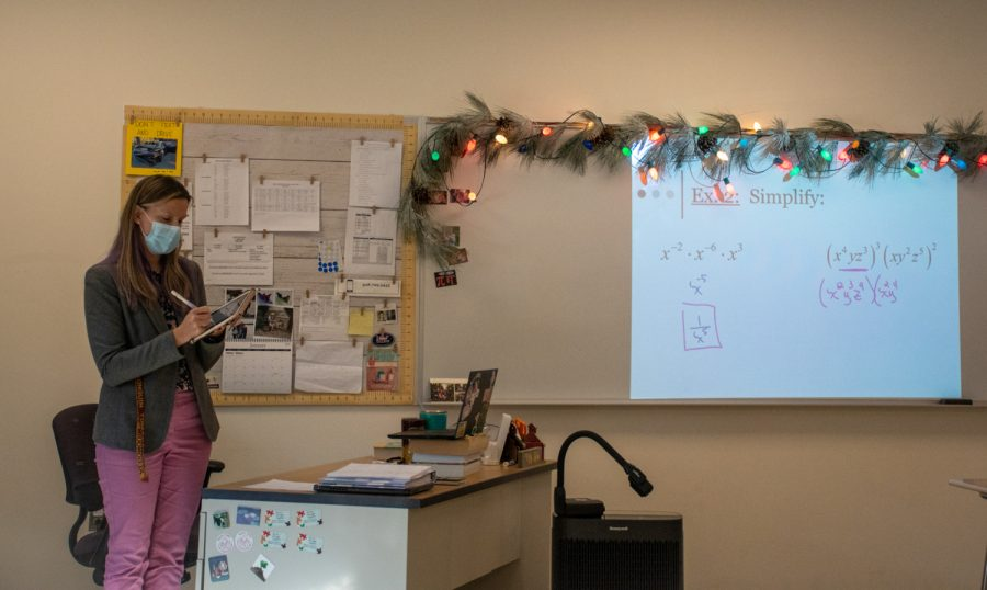 Math teacher Mary Rose Steele writes down solutions to exponential expressions on the board during a hybrid day which allows for in person learning.