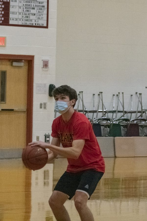 Senior captain Patrick Freeman prepares to shoot the ball during boys' basketball tryouts.