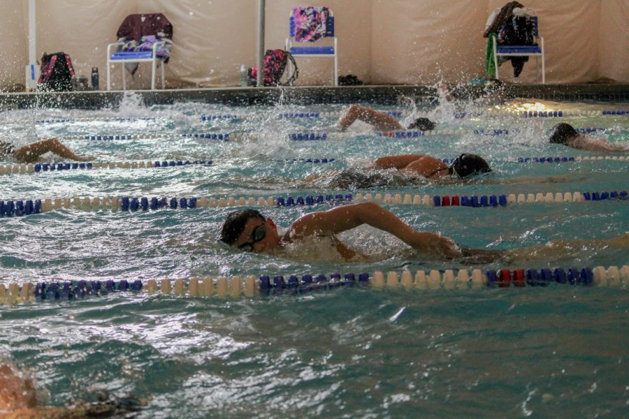 In between heats, swimmers stay warm by doing practice drills such as this one during the February 5 meet.