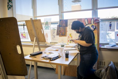 Senior Jasmine Castillo photographs her newly made artwork and later shows her friends.
