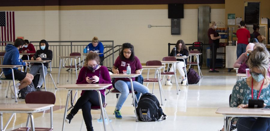 Students sit socially distant from each other in the cafeteria as well as in the C gym. Students are required to sit at recently cleaned desks and follow social distancing guidelines put in place to limit contact.