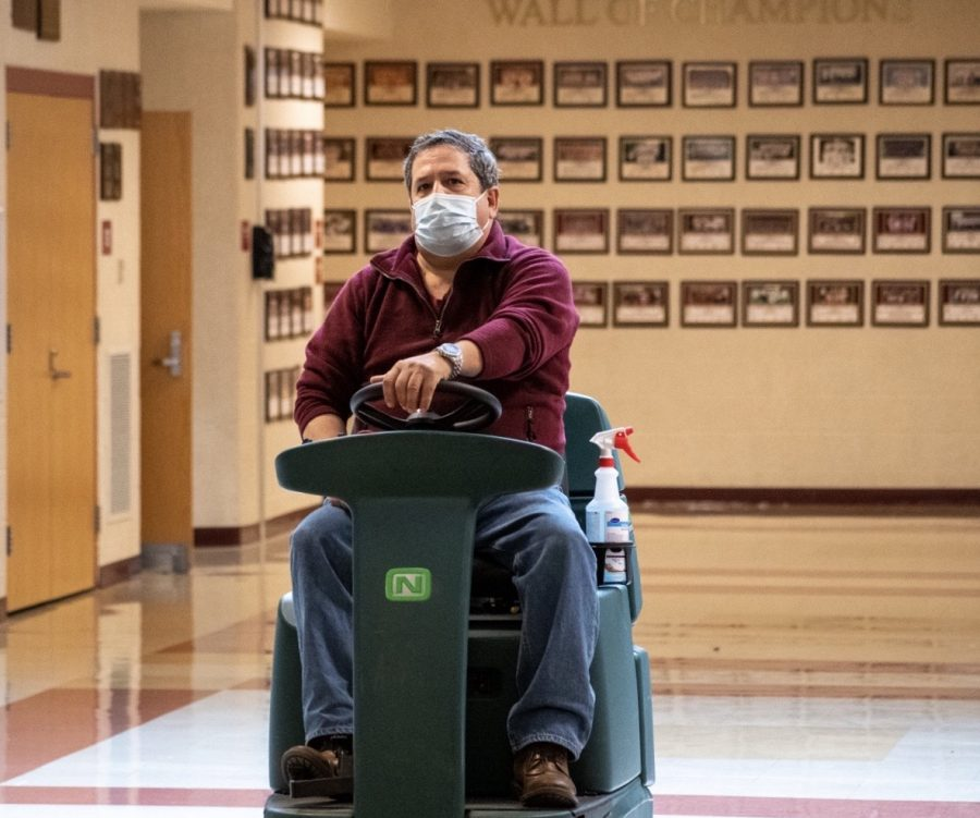 Custodian Armando Bairos cleans the gym lobby. Throughout the evening Armando oversees the school cleaning contractors along with events held at Algonquin.