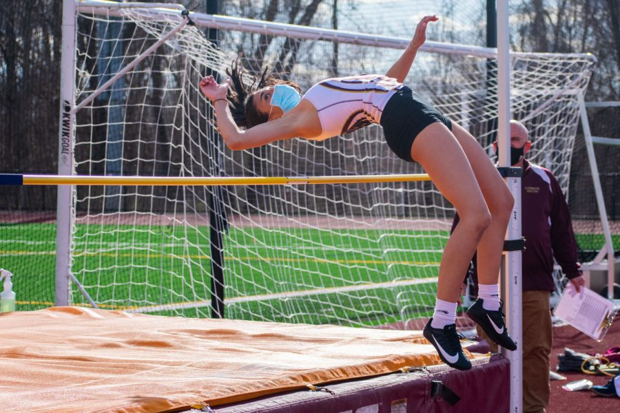 Junior Priscilla Decarvalho attempts to clear the high jump bar at the girls indoor track meet at Sheppard Hill on April 6. Indoor track meets were held outdoors this season to maximize the safety of student-athletes.