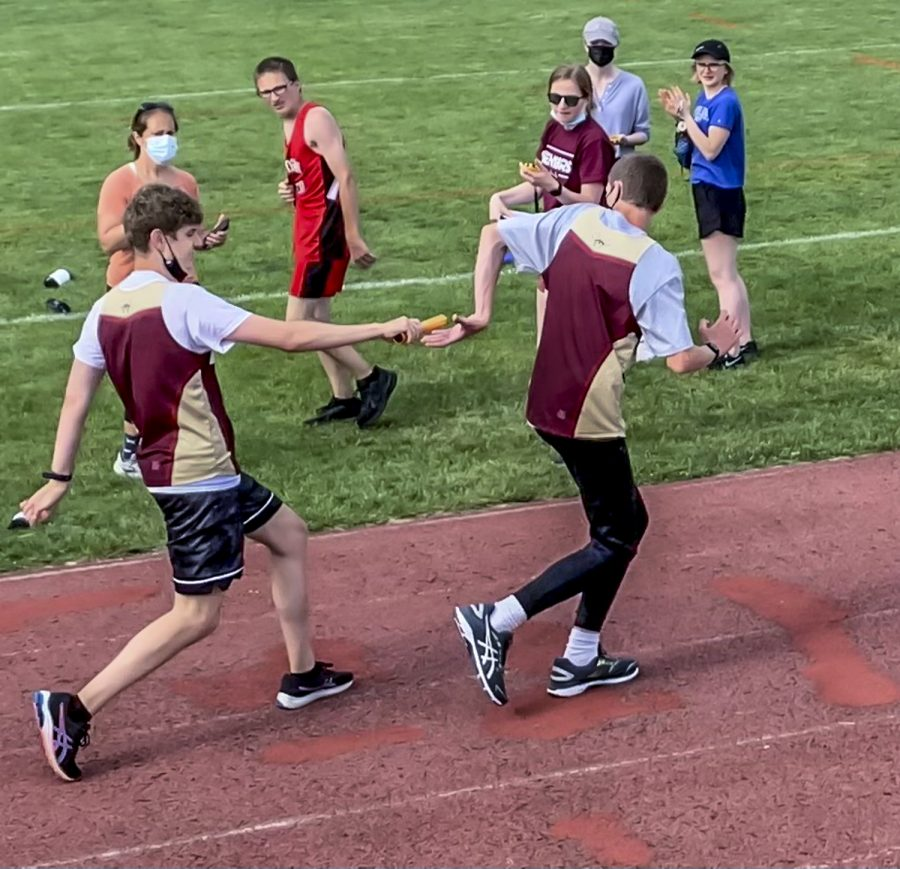 """Junior Andreas Bello hands off the baton to Junior Tobin Moore in a relay event in the Unified Track meet against Hudson High School on Wednesday, June 2 at home. Moore has enjoyed meeting new people as part of the team, and said, """"I hope to keep improving my scores."""""""