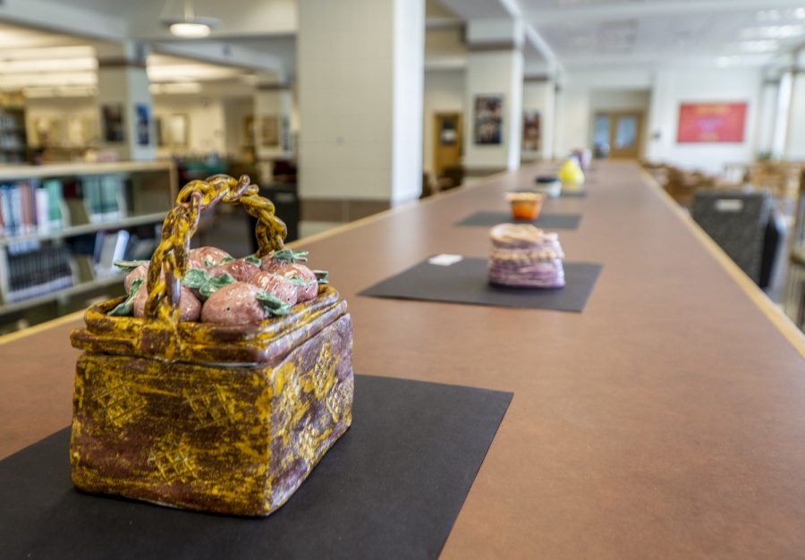 Art made by Ceramics I students are displayed on bookshelves in the library.