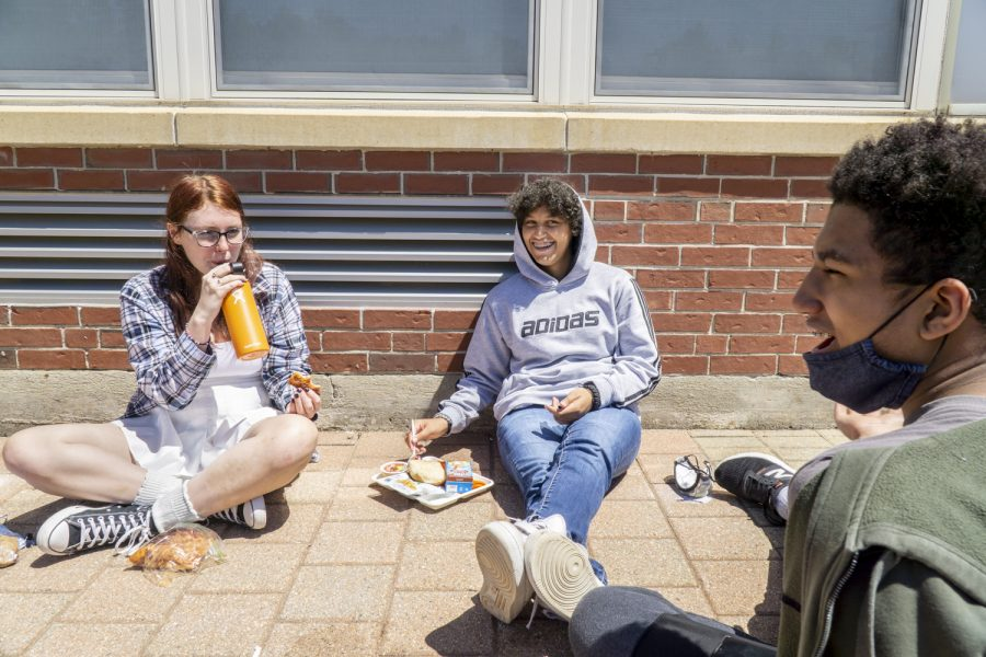 Freshmen Taylor Queenan, Hunter Lopez and Jayden Edwards chat while eating their lunches. As public areas reopen, many people are able to go outside without a mask for the first time in a while.