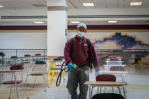 ARHS facility member Jon Souza flashes a quick smile through his mask while sanitizing the cafeteria.