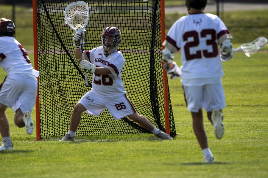Junior goalie Colin Connors attempts to stop his opponent from scoring. On June 1, Algonquin defeated Gronton-Dunstable 12-6.