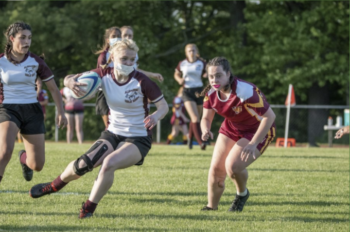 Junior Colleen Mulligan clutches the ball as she runs around a Weymouth defender.