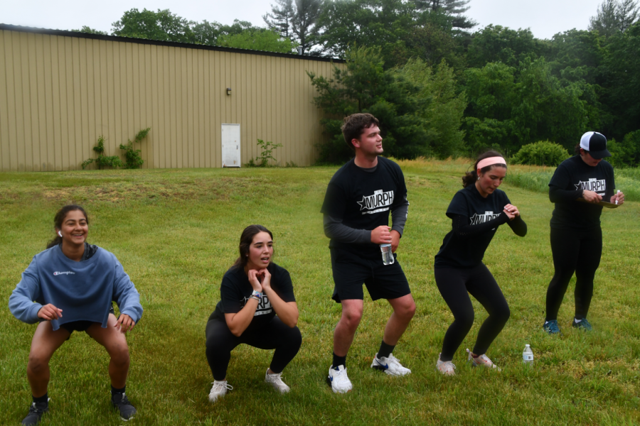 Five participants do squats in the 2021 Murph Challenge held on May 31 at Lamy Automotive in Northborough.