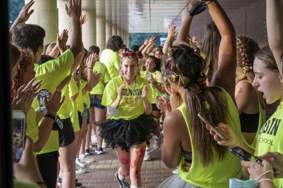 Senior Kristina Callahan runs down the gauntlet of senior peer mentors leading the incoming freshmen to the gym. The gauntlet is an annual tradition where upperclassmen mentors cheer as freshmen enter the building.