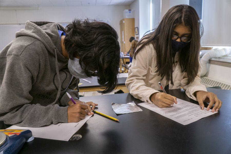 Sophomores Abhaya Sundar and Lipi Niyogi work on their lab during their Chemistry class.