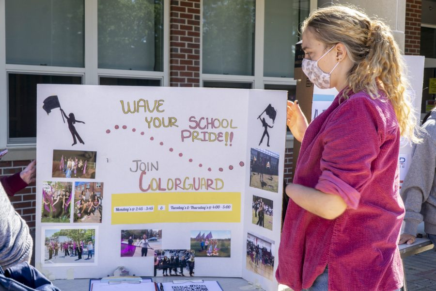 A student stands in front of the ARHS Colorguard stand at the club fair.