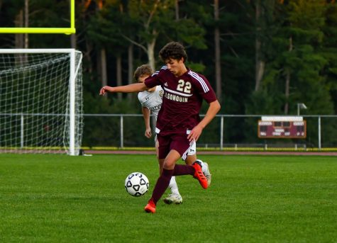 Trying to keep the ball from his opponent, sopomore David Downey runs down the field. Algonquin defeated Shrewsbury 3-0.