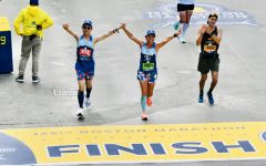 Senior Enchee Xu and his mother, Connie Cao, triumphantly cross the finish line, hand-in-hand, after running the entire Boston Marathon together.